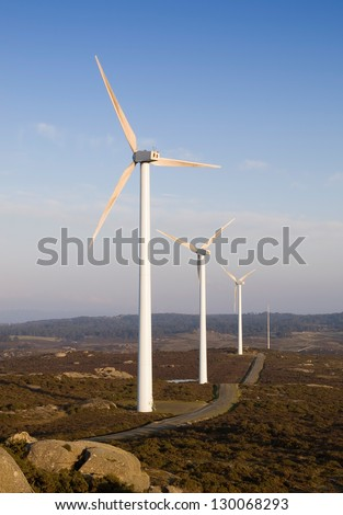 Wind turbines in a landscape at sunset. - stock photo