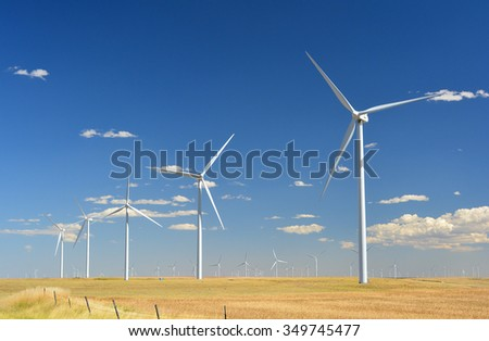 Wind Turbines in a Plowed Farmer's Field on a Sunny Day - stock photo