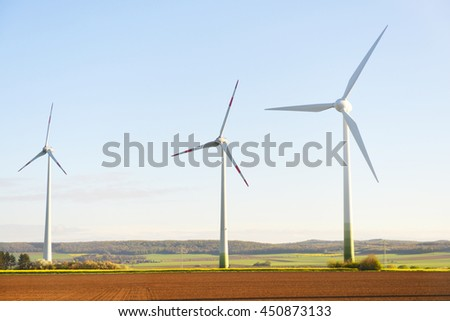 wind turbines in  fields under blue sky - stock photo