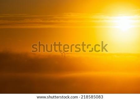 Wind turbines in misty sunrise - stock photo
