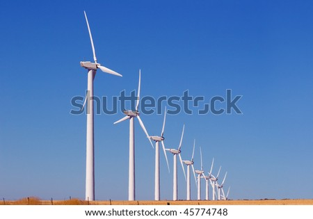 Wind turbines in row against clear blue sky - stock photo