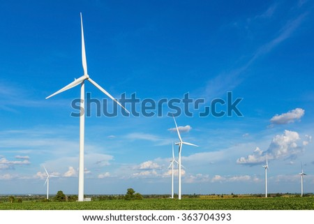 Wind turbines in the field against blue sky generating electricity - stock photo