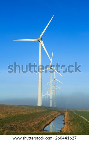 Wind turbines on a dike generating clean energy on a foggy morning in the countryside. - stock photo