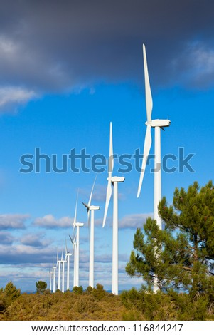 Wind turbines on a wild field in Spain. Vertical shot - stock photo