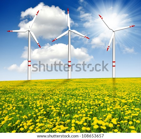wind turbines on dandelion field with sunny sky - stock photo