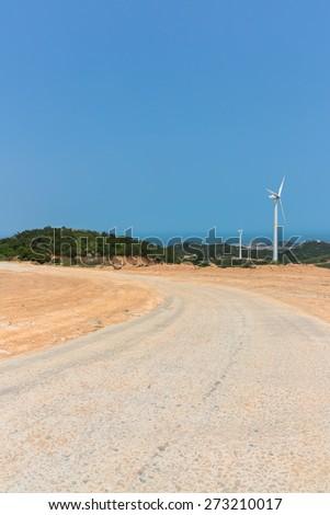 Wind turbines on landscape along empty road against sky. - stock photo