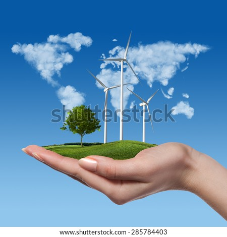 Wind turbines on meadow with tree holds in womans hand against blue sky and map of the world made of clouds. Worldwide Green energy concept - stock photo