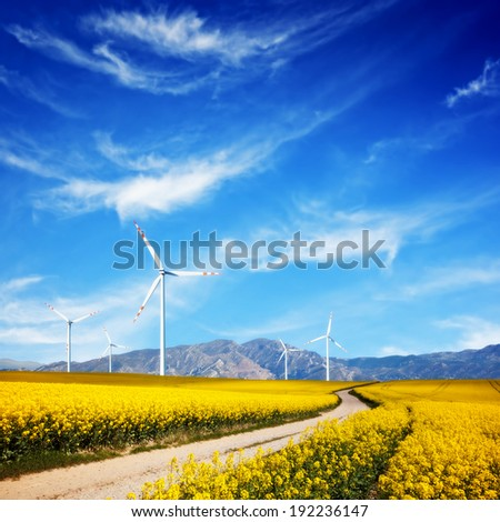 Wind turbines on spring field. Alternative, clean and natural source of energy is gaining pupularity. Eco farm. - stock photo