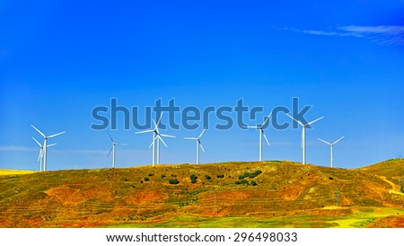 Wind turbines on the green hill in front of blue sky and power lines with poles at summer sunny weather - stock photo