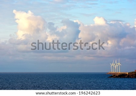 wind turbines on the sea with beautiful clouds - stock photo
