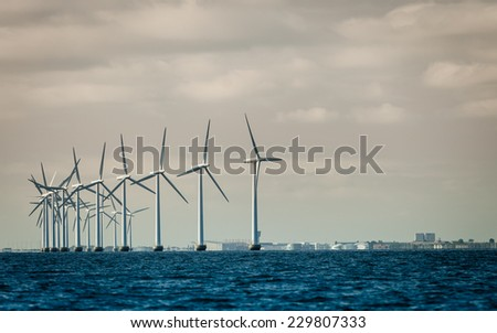 wind turbines power generator farm for renewable energy production along coast baltic sea near Denmark. Alternative green energy ecology. - stock photo