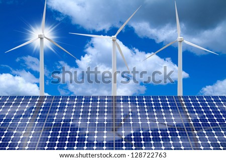 Wind turbines reflecting on solar panels with sun and blue cloudy skies - stock photo