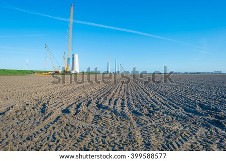Wind turbines under construction along a dike - stock photo