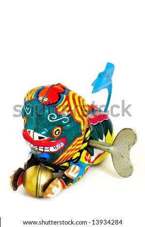 Wind-up toy dragon from China with blue tail and a golden ball in its paws, made of brightly-painted metal.  The winding key is visible in its side. - stock photo