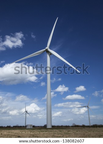 Windfarm showing group of wind turbines against blue sky and clouds - stock photo