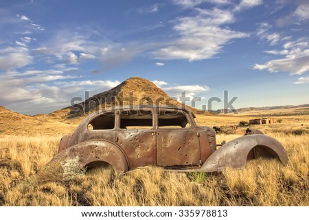 WINDHOEK, NAMIBIA- OCTOBER 20,  2012: Historic car wreck with bullet holes stands in the abandoned back country.  An information sign describes a shooting in the 19th century - stock photo