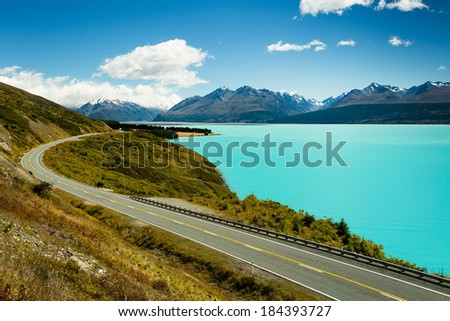 Winding asphalt mountain road near Lake Pukaki view from Glentanner Park Centre near Mount Cook, on a background of blue sky with clouds, snowy Southern Alps.  - stock photo