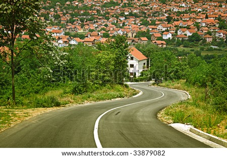 Winding countryside road leading down to town. - stock photo