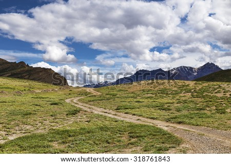 Winding dirt road among green meadows going to snow peaks - stock photo