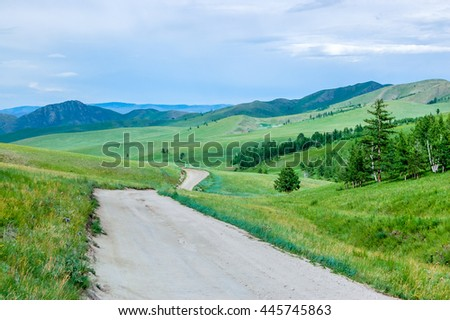 Winding dirt road through lush rolling hills of central Mongolian steppe - stock photo