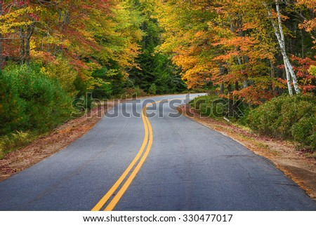 Winding road curves through colorful autumn trees in New England - stock photo