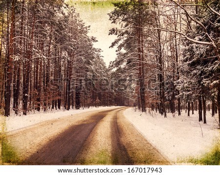 Winding road hidden behind tall pine trees, frosty winter landscape - stock photo
