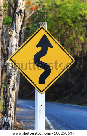 winding road sign in yellow and black - stock photo