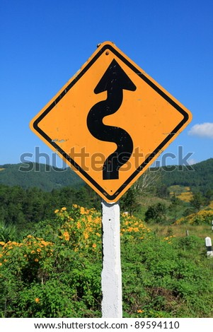 winding road sign in yellow and black on blue sky background - stock photo