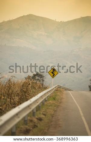 Winding Road Sign on asphalt road - stock photo
