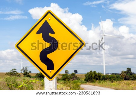 Winding road sign with windmill background in wind farm, Korat province in Thailand. - stock photo