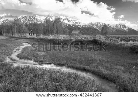 Winding stream and an old farm in the Tetons, Wyoming, USA. - stock photo