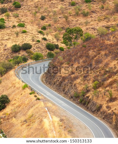 Winding tarred road in the countryside snaking through dry hilly terrain viewed from above - stock photo