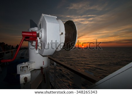 Windlass of lifeboat at sunrise - stock photo