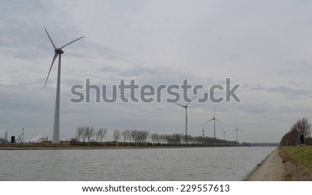 Windmill alley is stretched alongside water channel inside the grounds of port of antwerp. - stock photo