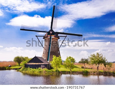 Windmill by river in Netherlands - stock photo