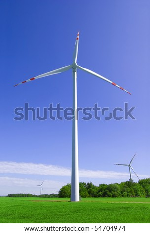 Windmill conceptual image. Windmill on the green field against the blue sky. - stock photo