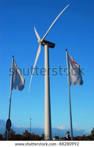 Windmill for energy production near flags - stock photo