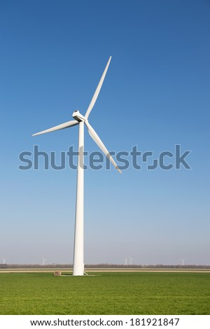 Windmill for wind energy in the grass fields - stock photo
