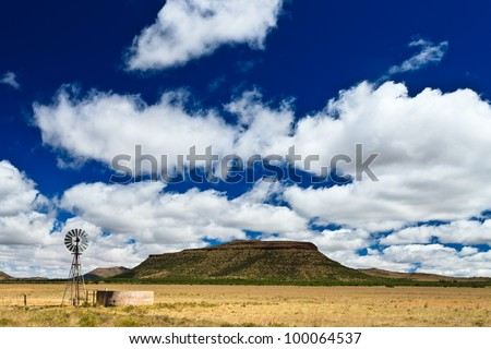 Windmill in a desolate landscape with beautiful cloudscape in Africa - stock photo