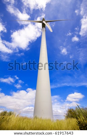 Windmill in a field against a blue sky and clouds, alternative energy source - stock photo