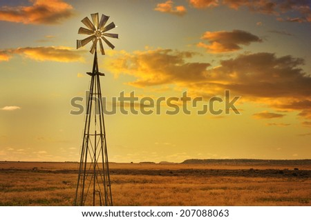 Windmill in African savannah landscape and beautiful sunset - stock photo
