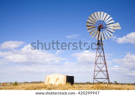 Windmill in Queensland, Australia, with blue sky and fluffy white clouds - stock photo