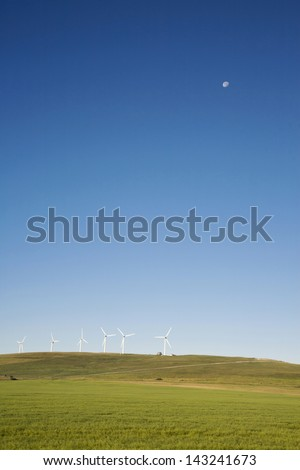 Windmill in the field with blue sky and moon background - stock photo