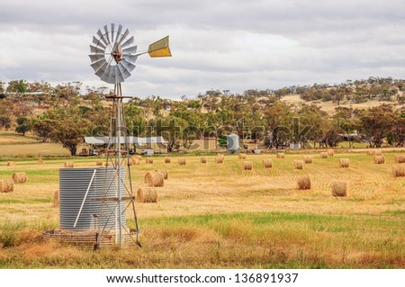 windmill in the field with hay and straw bales in the end of summer - stock photo
