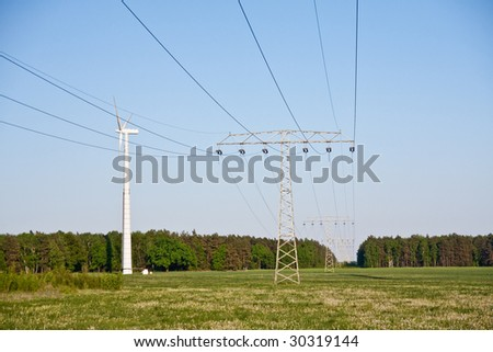 windmill together with high voltage powerlines - stock photo