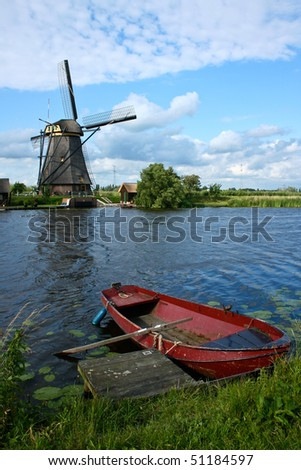 Windmill with Red boat in Holland - stock photo