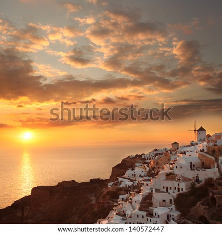 Windmills against colorful sunset in  Santorini, Greece - stock photo