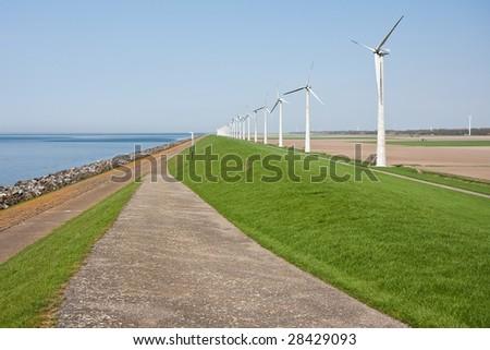 Windmills along the dike - stock photo