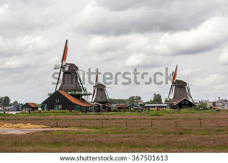 Windmills and rural houses in Zaanse Schans near Amsterdam, Netherlands - stock photo