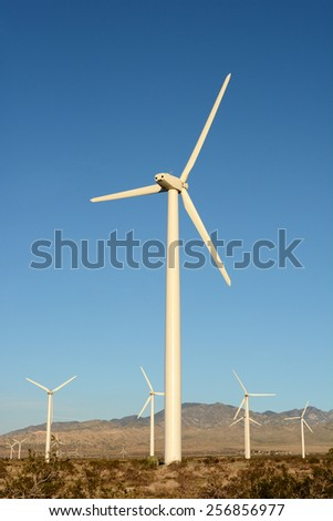 Windmills at a wind farm near Palm Springs, California . Vertical format with warm light. - stock photo